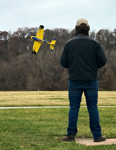 A man flying a remote-controlled model aircraft